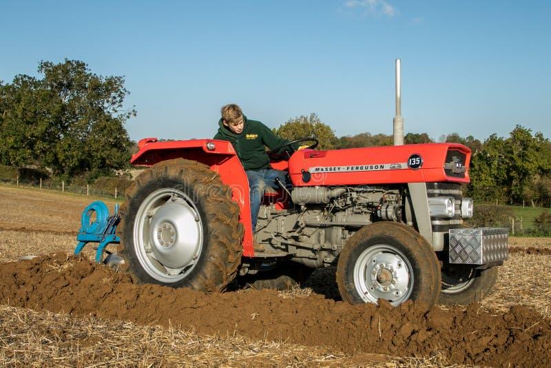Muchacho joven con el arado rojo del tractor del vintage fotos de archivo libres de regalías