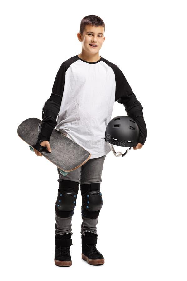 Muchacho joven con el equipo protector y un monopatín foto de archivo