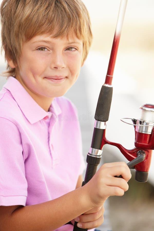 Muchacho joven con la barra de pesca imagen de archivo libre de regalías