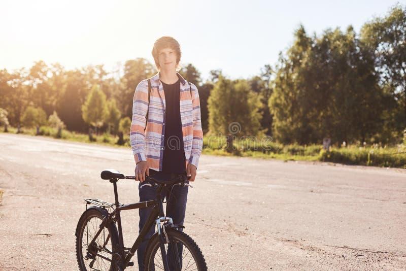 Muchacho joven con la camisa que lleva del peinado elegante y vaqueros que se colocan con la bicicleta que tiene viaje que admira imagen de archivo libre de regalías