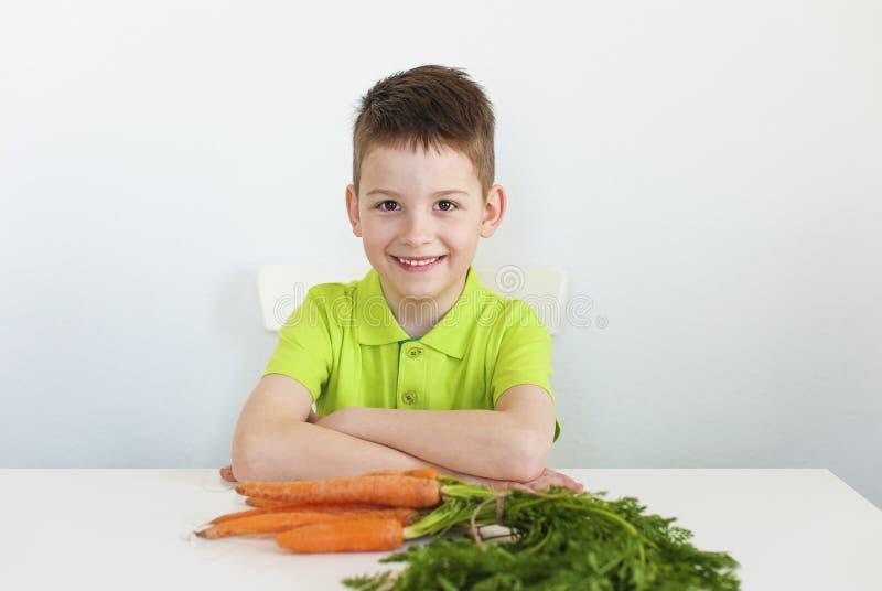 Muchacho joven con la zanahoria imagenes de archivo