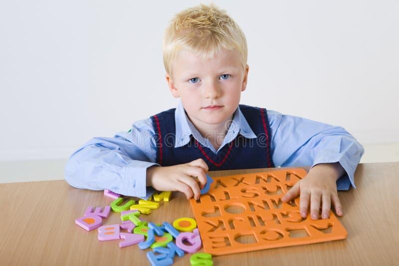 Muchacho joven con los rompecabezas de las cartas fotografía de archivo