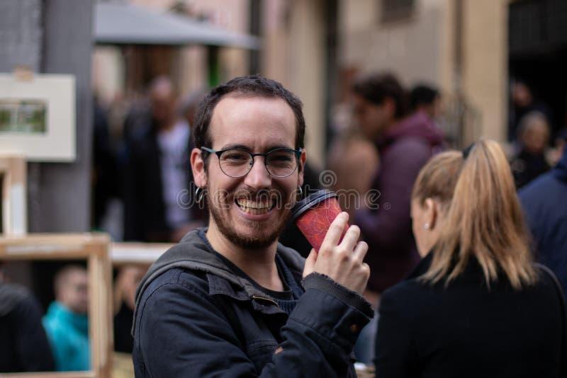Muchacho joven con sonrisas de los pendientes mientras que bebe un café en la calle foto de archivo libre de regalías