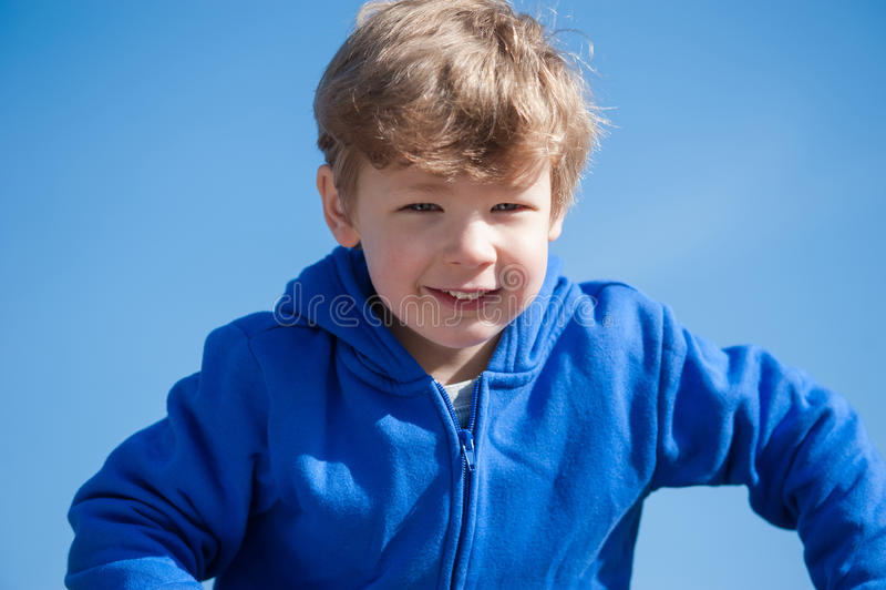 Muchacho joven contra un cielo azul fotografía de archivo