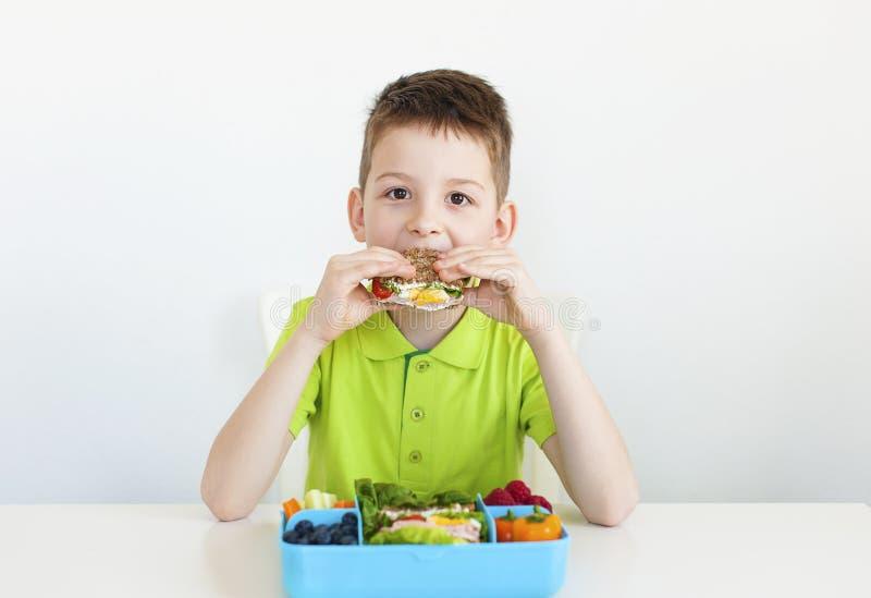 Muchacho joven de 8 años que come la comida sana imagen de archivo libre de regalías