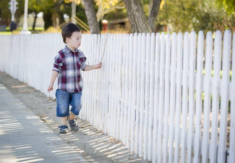 Muchacho joven de la raza mixta que camina con el palillo a lo largo de la cerca blanca imágenes de archivo libres de regalías