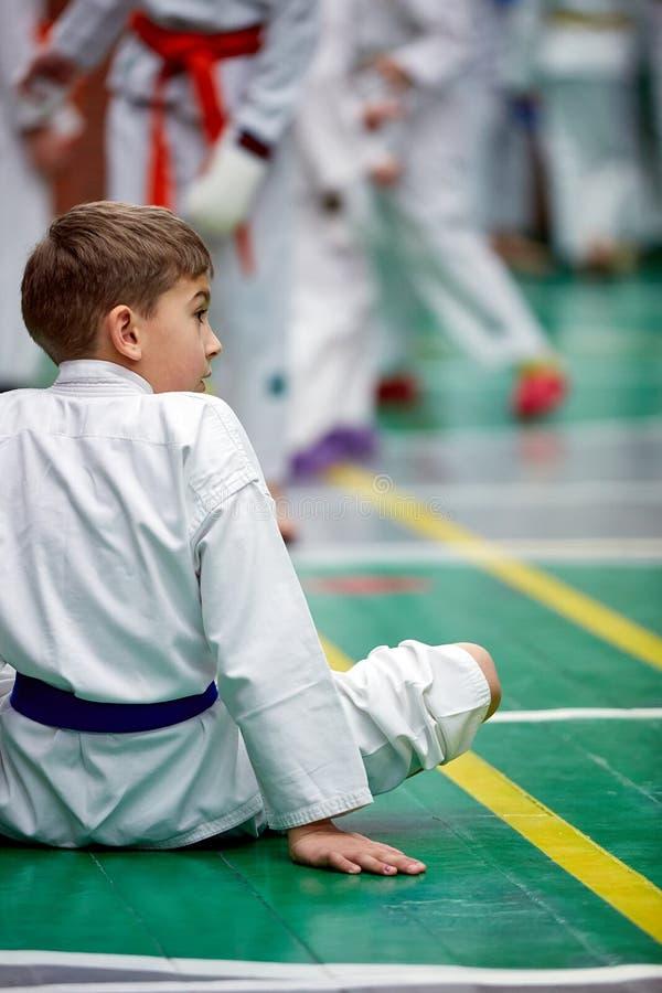 Muchacho joven del karate que calienta en un kimono fotografía de archivo