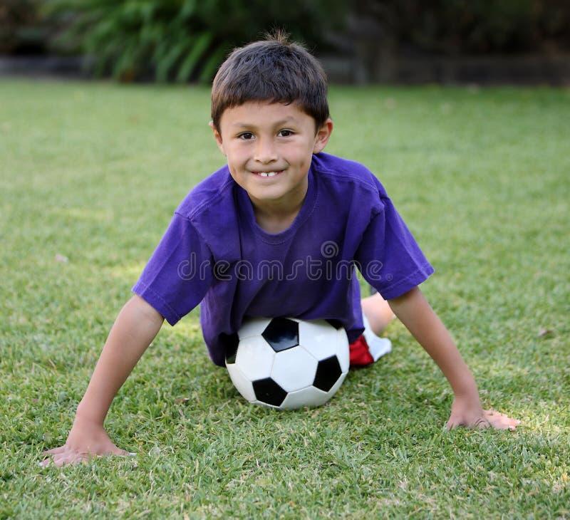 Muchacho joven del latino con el balón de fútbol imagen de archivo