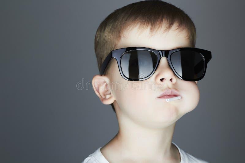 Muchacho joven divertido que come una piruleta Niño en gafas de sol foto de archivo