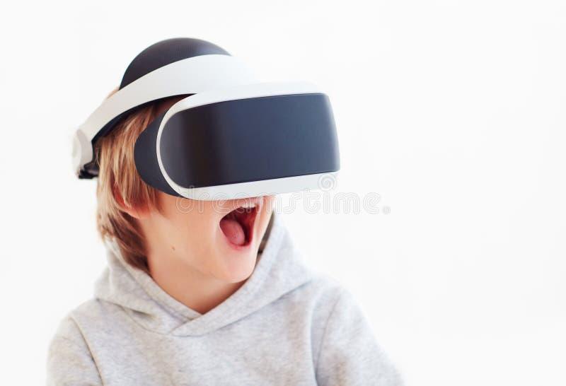 Muchacho joven emocionado, niño que lleva las gafas de la realidad virtual, jugando videojuegos fotografía de archivo