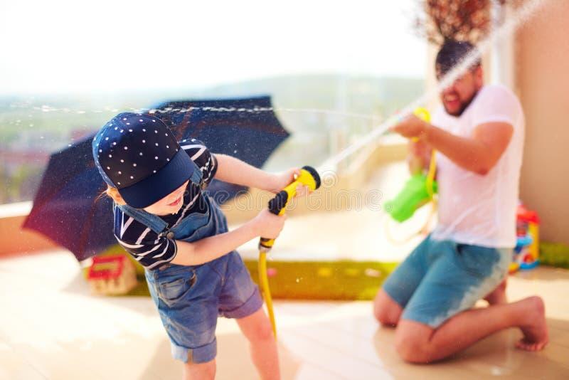 Muchacho joven emocionado que se divierte, salpicando el agua con el padre en el día de verano caliente fotografía de archivo