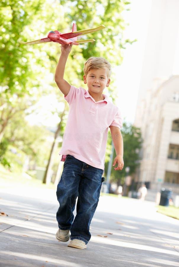 Muchacho joven en calle con el avión del juguete imagenes de archivo
