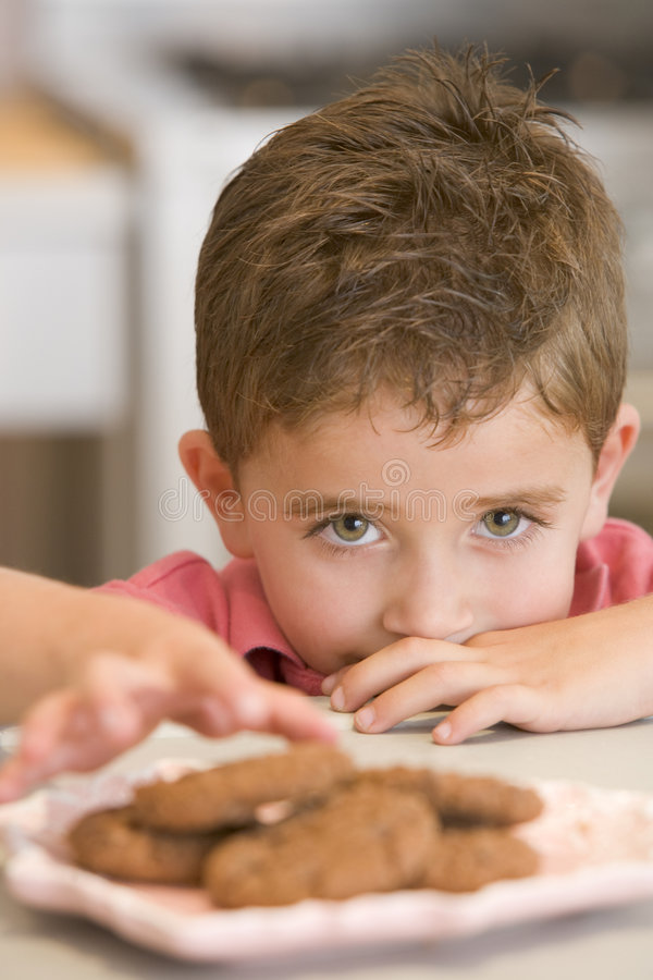 Muchacho joven en cocina que come las galletas imagenes de archivo