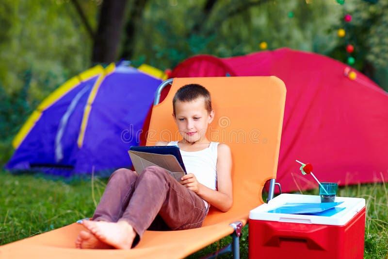 Muchacho joven en el campamento de verano, relajándose con la tableta imagen de archivo