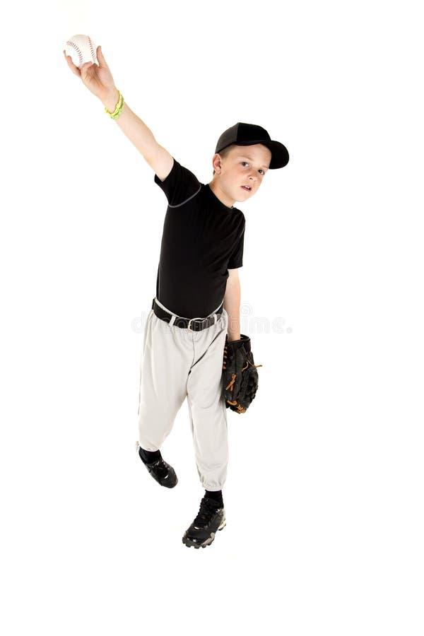 Muchacho joven en el uniforme que echa un béisbol derecho foto de archivo