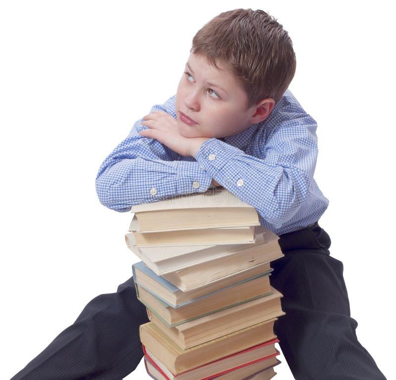 Muchacho joven en el vestido clásico que se sienta con el montón de libros fotos de archivo libres de regalías