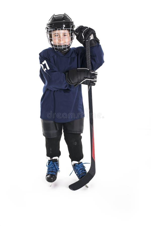 Muchacho joven en engranaje del hockey sobre hielo contra blanco foto de archivo libre de regalías