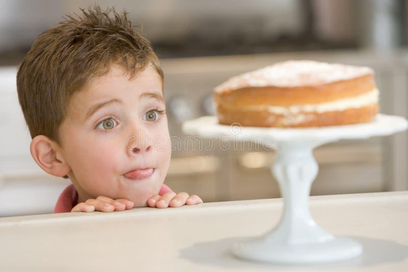Muchacho joven en la cocina que mira la torta en contador foto de archivo