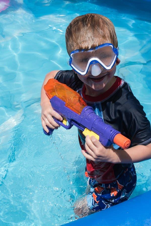 Muchacho joven en la máscara de la nadada que sostiene el arma de agua en piscina fotos de archivo