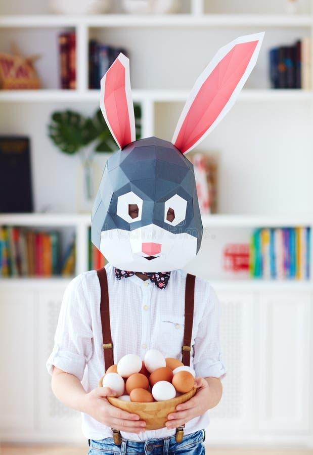 Muchacho joven en la máscara poligonal del conejo de conejito de pascua que presenta con un cuenco por completo de huevos fotografía de archivo libre de regalías