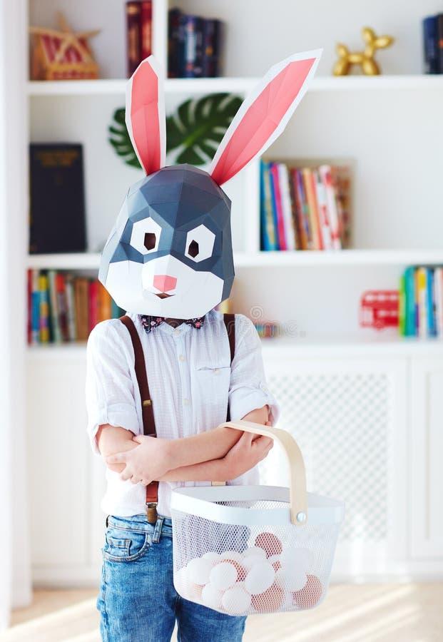 Muchacho joven en la máscara poligonal del conejo de conejito de pascua que presenta con una cesta por completo de huevos fotografía de archivo libre de regalías