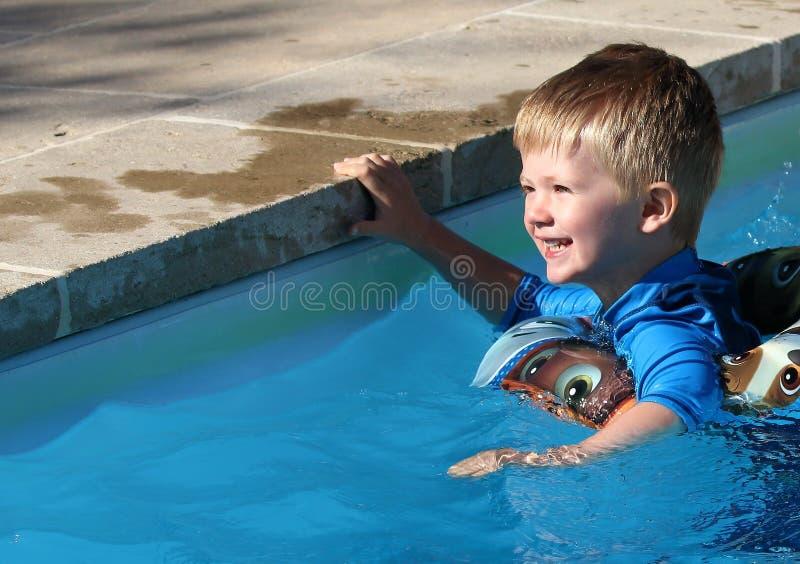 Muchacho joven en la piscina con un anillo de goma foto de archivo