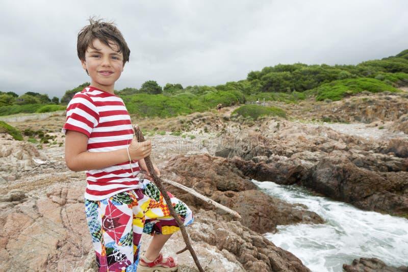Muchacho joven en las rocas delante del mar fotos de archivo