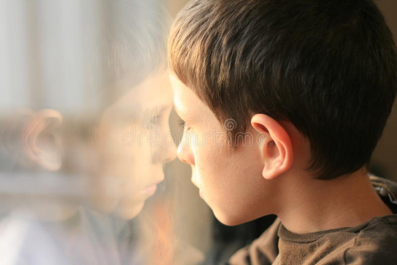 Muchacho joven en pensamiento con la reflexión de la ventana foto de archivo