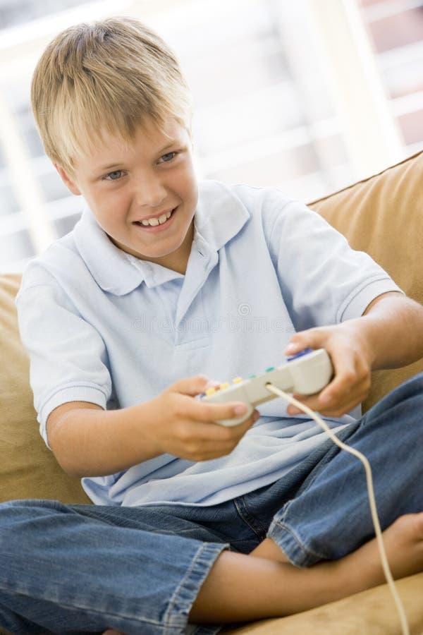 Muchacho joven en sala de estar con el juego video fotos de archivo