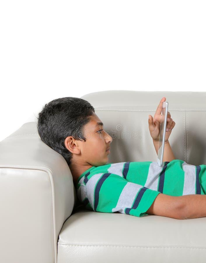 Muchacho joven en un sofá que mira fijamente intenso en su tableta imágenes de archivo libres de regalías