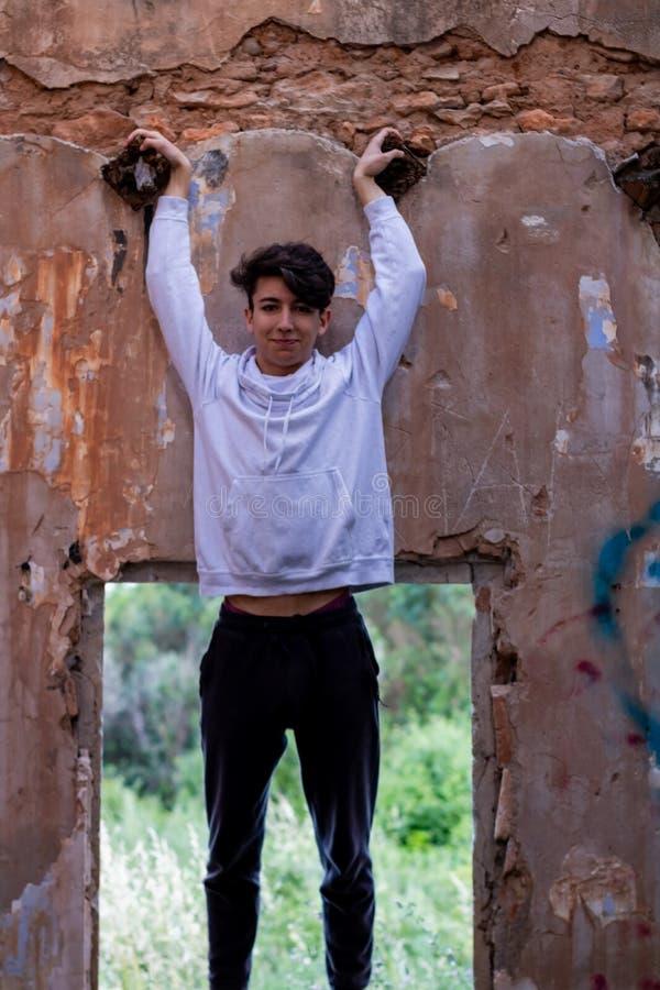 Muchacho joven en una casa abandonada fotos de archivo
