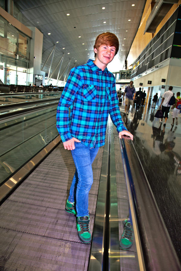 Muchacho joven en una escalera móvil dentro del aeropuerto imágenes de archivo libres de regalías