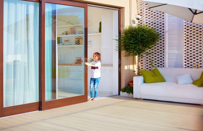 Muchacho joven feliz, abertura del niño la puerta deslizante en área del patio del tejado en casa fotos de archivo libres de regalías