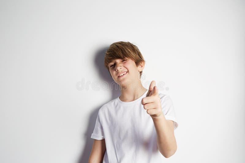 Muchacho joven feliz en la camiseta blanca que presenta delante de la pared vacía blanca Retrato del ni?o masculino de moda Mucha foto de archivo