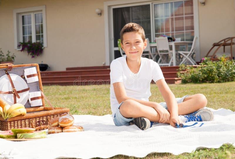 Muchacho joven feliz en la comida campestre fotografía de archivo libre de regalías