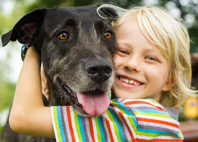 Muchacho joven feliz que abraza cariñosamente su perro casero foto de archivo
