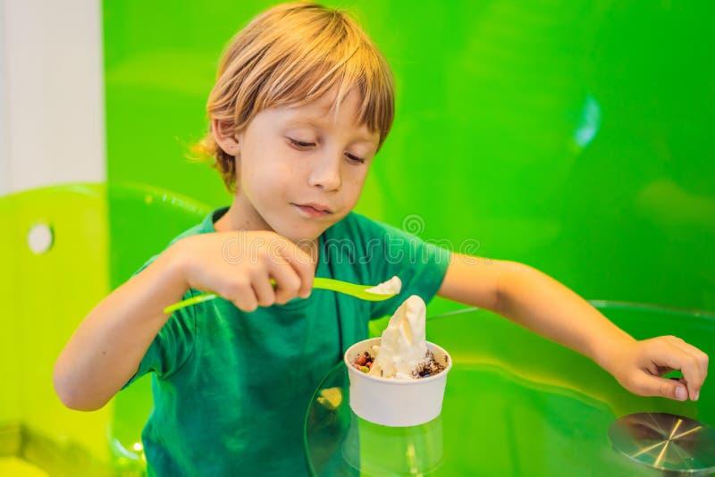 Muchacho joven feliz que come un helado sabroso o un yogurt congelado fotos de archivo libres de regalías
