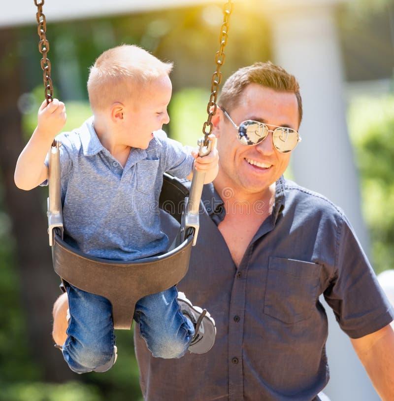 Muchacho joven feliz que se divierte en los oscilaciones con su padre foto de archivo libre de regalías