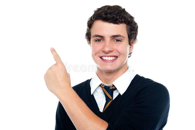 Muchacho joven hermoso en el uniforme que indica hacia arriba fotografía de archivo libre de regalías