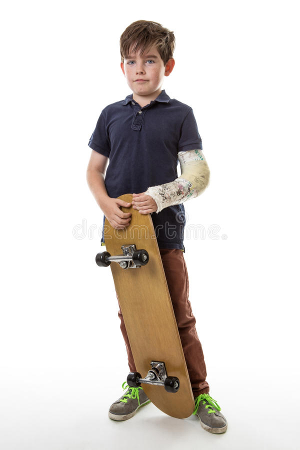 Muchacho joven lindo que sostiene un monopatín imagenes de archivo
