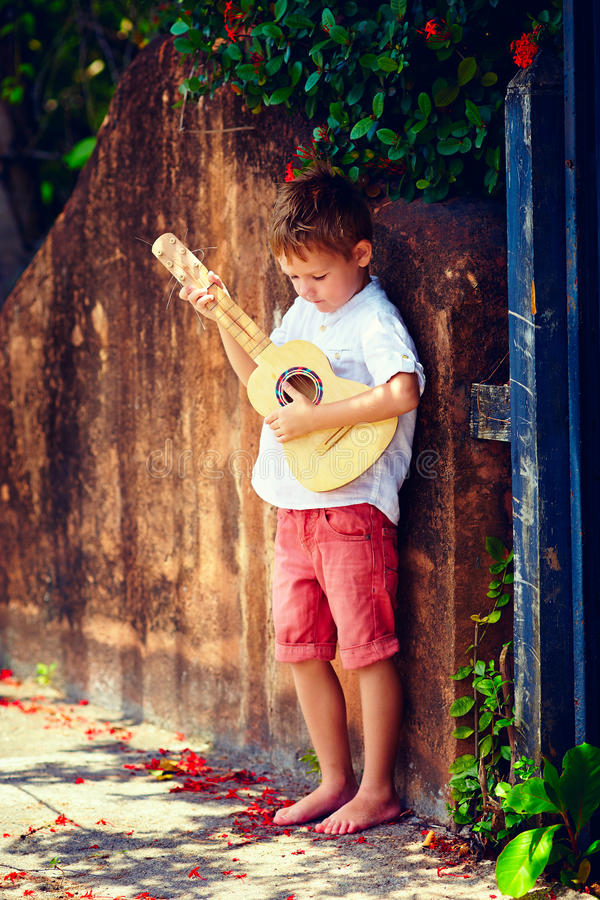 Muchacho joven lindo que toca la guitarra cerca de la cerca vieja del verano imagenes de archivo