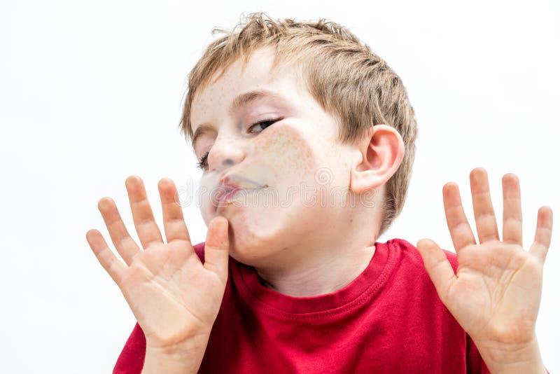 Muchacho joven machacado que toca su cara torpe a una ventana foto de archivo libre de regalías