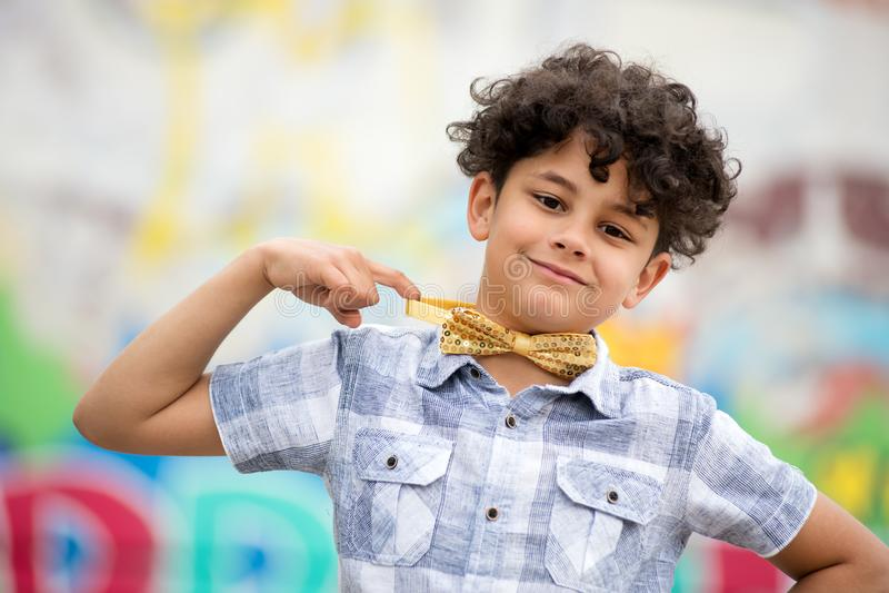 Muchacho joven orgulloso que señala a su corbata de lazo foto de archivo