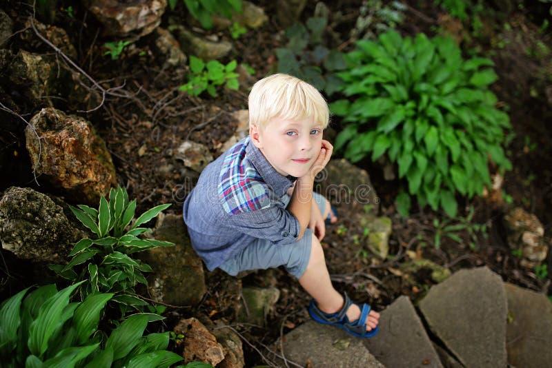 Muchacho joven pacífico que se sienta en jardín de piedras por las plantas verdes del Hosta foto de archivo libre de regalías