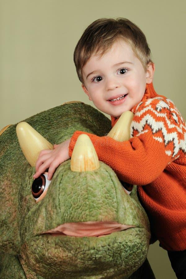 Muchacho joven que abraza el dinosaurio fotografía de archivo libre de regalías