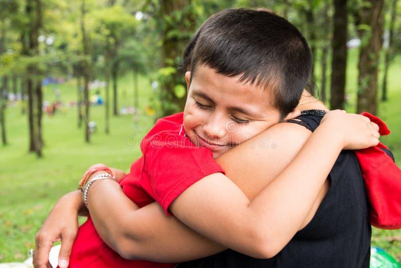 Muchacho joven que abraza a su madre en el parque con los ojos cerrados y el momento sonriente, feliz y blando de la niñez/del pa imágenes de archivo libres de regalías