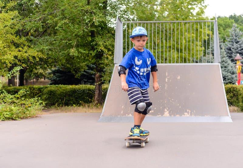 Muchacho joven que anda en monopatín en el parque imagen de archivo libre de regalías
