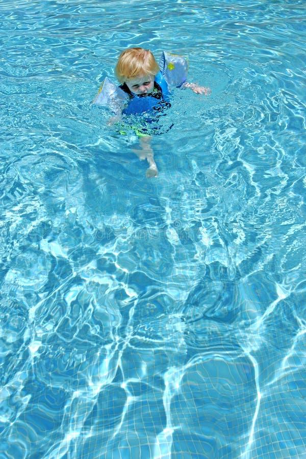 Muchacho joven que aprende nadar en piscina imágenes de archivo libres de regalías