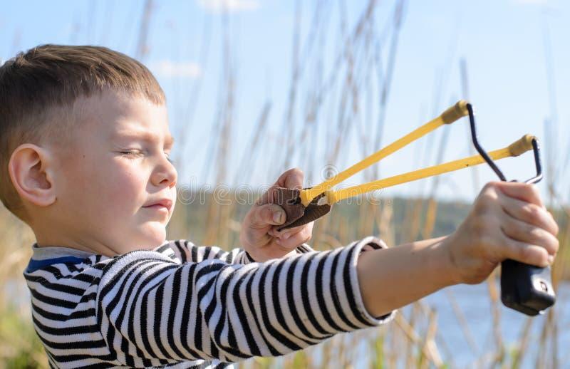 Muchacho joven que apunta el tiro de honda sobre el lago foto de archivo libre de regalías