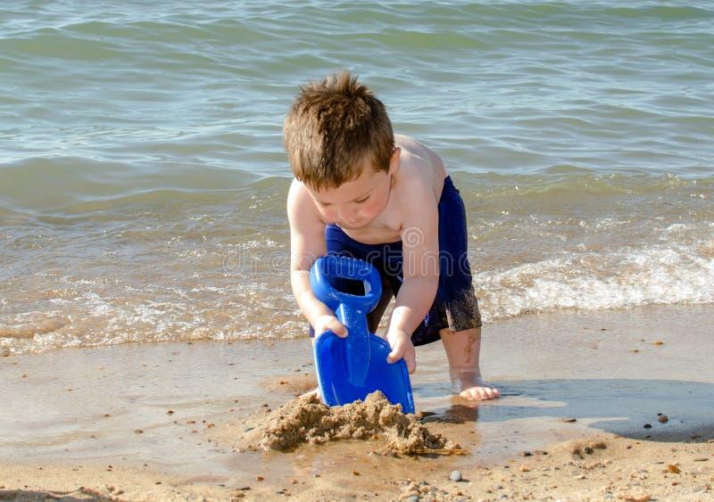 Muchacho joven que cava en la arena foto de archivo